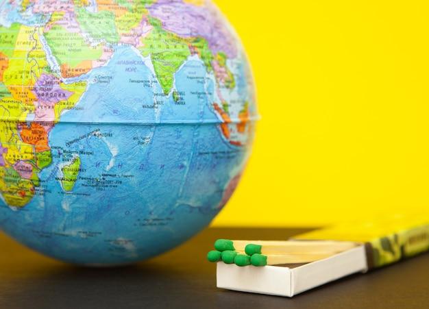 Fiammifero e globo del mondo su un giallo