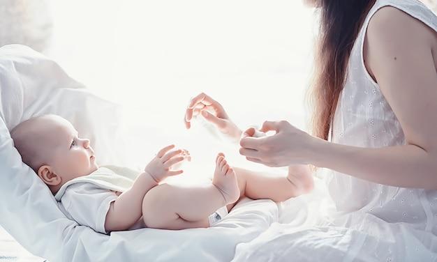 Concetto di maternità. una giovane madre allatta il suo piccolo bambino. primo richiamo e allattamento. famiglia numerosa in abiti bianchi.