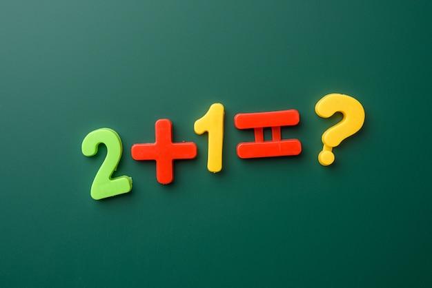 Esempio di matematica scritto su una lavagna verde, uno più due, da vicino