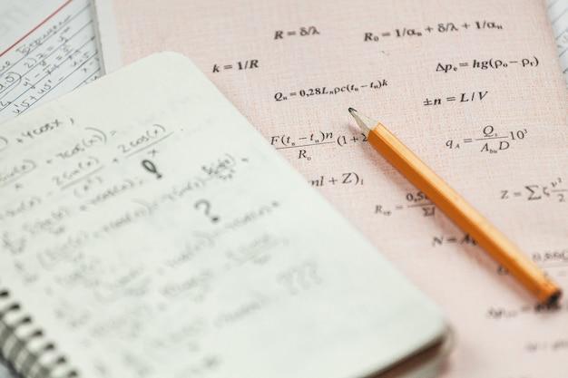 Le formule matematiche sono scritte a matita su un pezzo di carta, problemi di matematica