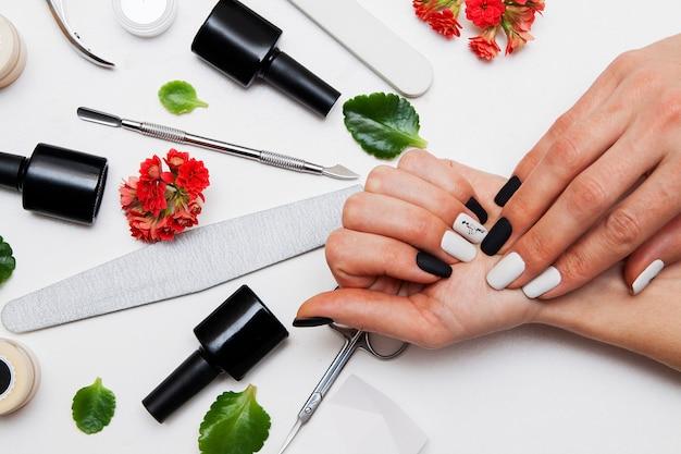 Manicure bianco e nero opaco sulle mani della donna
