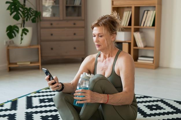 Donna attiva matura in abbigliamento sportivo con acqua dalla bottiglia di plastica e navigare in rete per nuovi corsi di fitness online per home sitter
