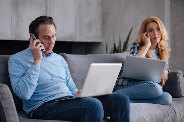 I dipendenti maturi coinvolti coppia seduta a casa e utilizzando smartphone e laptop durante la navigazione in internet e avere conversazioni di lavoro
