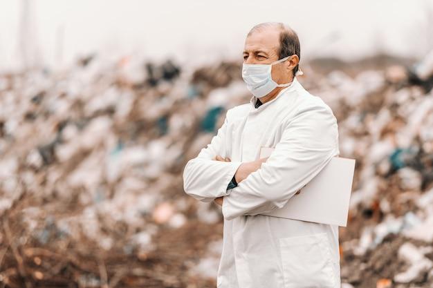 Maturo adulto ecologo caucasico in uniforme bianca e maschera sul viso in piedi con le braccia incrociate e tenendo appunti sotto l'ascella.