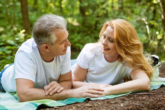 Coppia adulta matura felice nel parco abbracciando mentre è seduto sul plaid