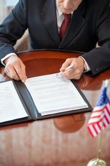 Delegato americano maturo in abiti da cerimonia che si china sul tavolo mentre esamina i termini e le condizioni del contratto di partnership commerciale