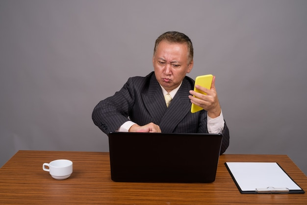 Uomo d'affari asiatico maturo che si siede con la tavola di legno contro il grigio