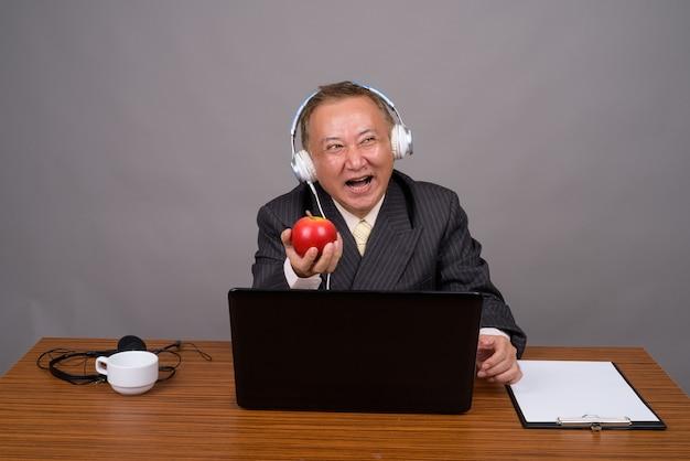 Uomo d'affari asiatico maturo che si siede con la tavola di legno contro gray