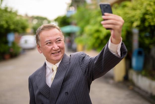 L'uomo d'affari asiatico maturo che utilizza il telefono cellulare nelle strade supera