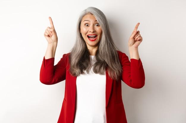 Matura imprenditrice asiatica con i capelli grigi, indossa un blazer rosso e punta il dito verso l'alto, sorridendo sorpreso, mostrando offerta promozionale, sfondo bianco.