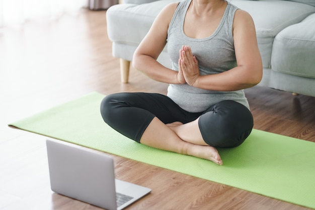 Una donna grassa e paffuta asiatica matura seduta sul pavimento in soggiorno pratica lezioni di yoga online con il computer. femmina che ha meditare la lezione di formazione sul laptop.