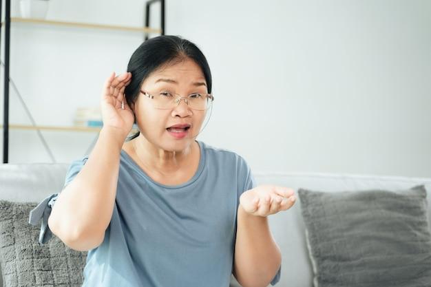 Una donna disabile sorda asiatica matura che ha problemi di udito tiene la mano sull'orecchio, ascolta attentamente, con problemi di udito.