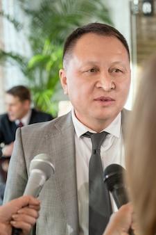 Delegato maschio asiatico maturo in abiti da cerimonia in piedi di fronte a giornalisti con microfoni e risponde alle loro domande durante l'intervista