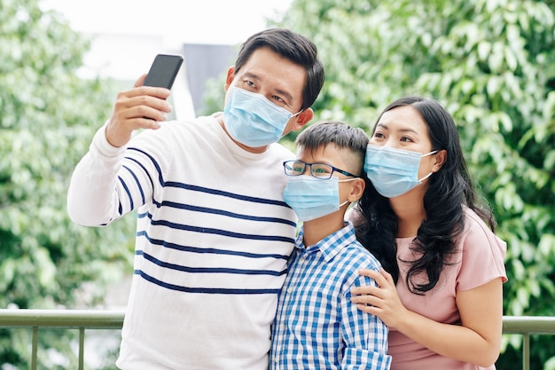 Uomo asiatico maturo che indossa una maschera medica a causa della pandemia di coronavirus e si fa un selfie con la moglie e il bambino preadolescenziale