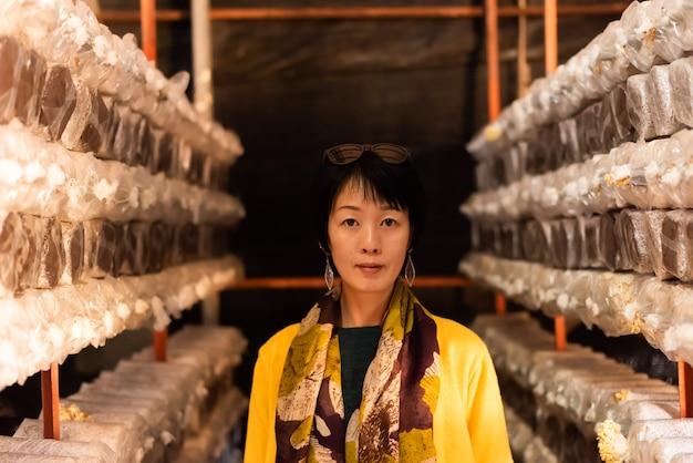 Una donna asiatica matura viaggia e visita una fattoria di funghi nella cittadina di puli, taiwan