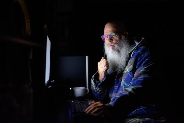 Uomo maturo calvo barbuto hipster che lavora straordinario a casa a tarda notte