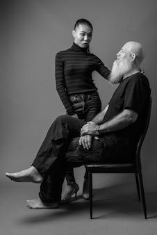 Uomo calvo barbuto maturo e giovane bella donna asiatica insieme contro il muro grigio in bianco e nero