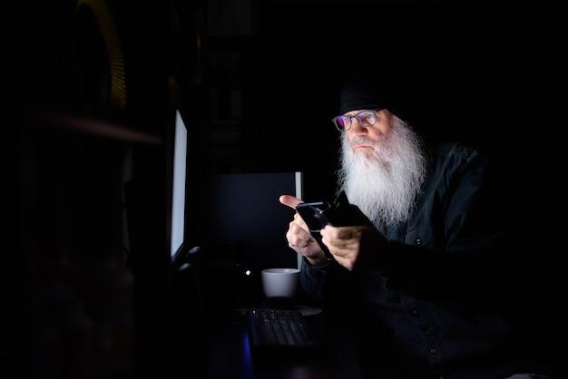 Uomo maturo barbuto hipster utilizzando il telefono mentre si fa gli straordinari a casa a tarda notte al buio
