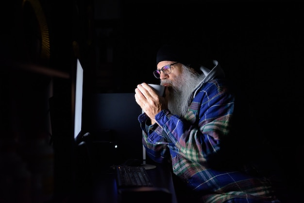 Uomo maturo barbuto hipster con occhiali bere caffè mentre si fa gli straordinari a casa al buio