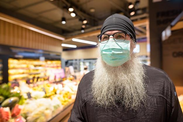 Uomo barbuto maturo dei pantaloni a vita bassa con i frutti d'acquisto della maschera al supermercato