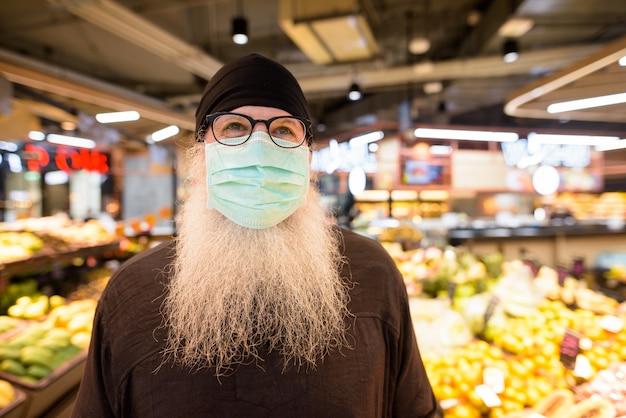 Uomo barbuto maturo dei pantaloni a vita bassa con acquisto della maschera nella sezione di frutti al supermercato