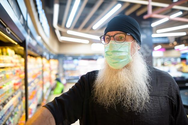 Uomo barbuto maturo dei pantaloni a vita bassa con acquisto della maschera con la distanza al supermercato