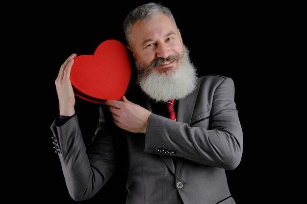 Coppia uomo barbuto indossare abito grigio tiene rosso a forma di cuore confezione regalo, isolato su sfondo nero