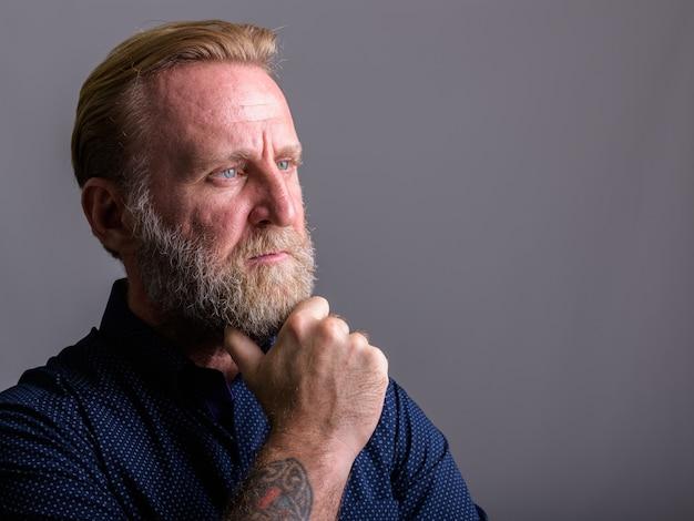 Uomo barbuto maturo con tatuaggi a mano pensando