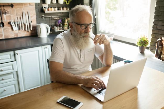 Maturo uomo barbuto con laptop e occhiali