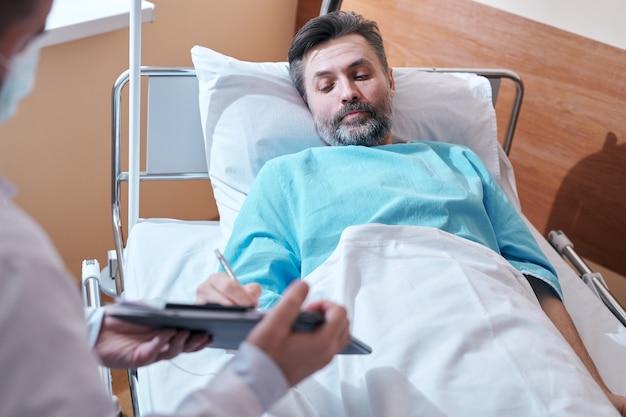 Paziente barbuto maturo in abito ospedale sdraiato a letto e firma accordo medico mentre dà il consenso all'intervento chirurgico