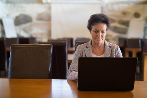 Matura bella imprenditrice utilizzando il computer portatile presso la caffetteria