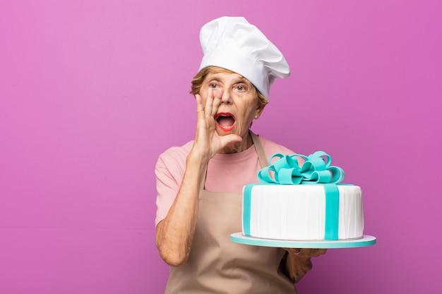 Matura bella donna anziana che si sente felice, eccitata e positiva, gridando con le mani vicino alla bocca, chiamando