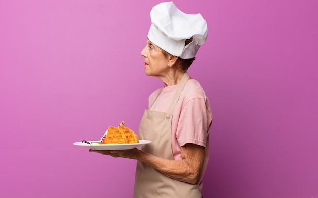 Bella donna anziana matura sulla vista di profilo che cerca di copiare lo spazio davanti, pensare, immaginare o sognare ad occhi aperti