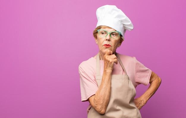 Bella donna anziana matura che pensa, si sente dubbiosa e confusa, con diverse opzioni, chiedendosi quale decisione prendere