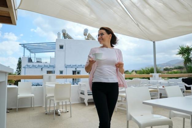 Matura bella donna che cammina con una tazza di caffè in hotel resort ristorante all'aperto. bellissimo e pittoresco paesaggio di montagna. ricreazione, tempo libero, estate, fine settimana, turismo, viaggi persone di mezza età