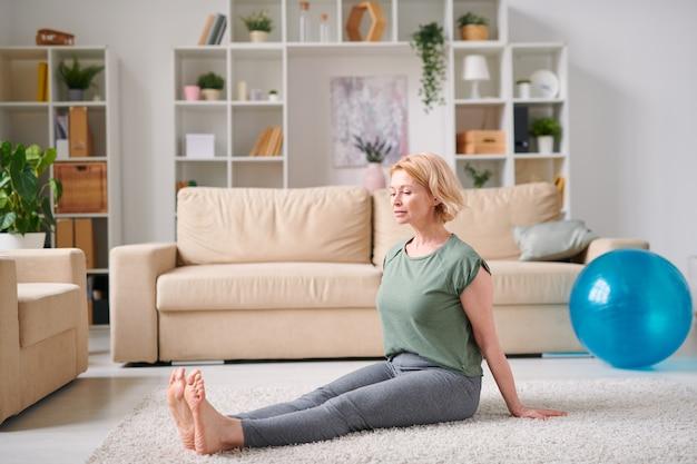 Donna attiva bionda matura in abiti sportivi che si siede sul pavimento e si esercita in soggiorno mentre si resta a casa per la quarantena