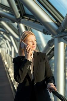 Femmina bionda matura delegata o imprenditrice in abiti da cerimonia parlando al telefono cellulare davanti alla telecamera all'interno del business center contemporaneo