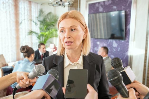 Delegata bionda matura in abiti da cerimonia in piedi di fronte a giornalisti con microfoni e risponde alle loro domande durante l'intervista