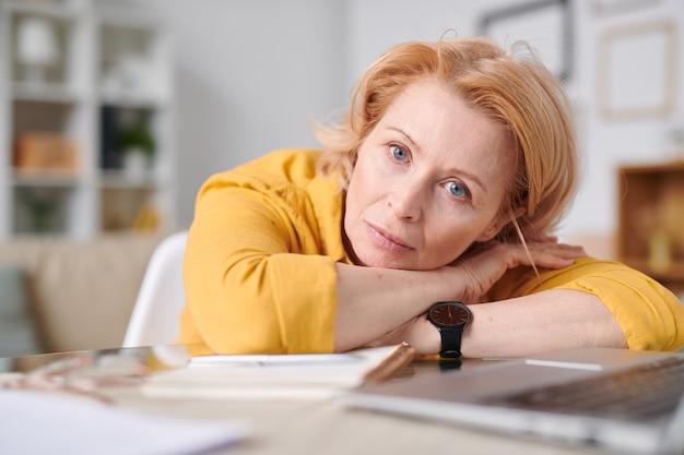 Donna di affari isolata auto bionda matura che ti guarda mentre giaceva sulla scrivania davanti al computer portatile durante il lavoro a distanza a casa