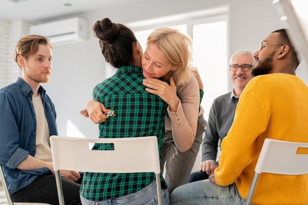 Donna bionda matura che abbraccia uno dei giovani compagni di gruppo dopo aver condiviso il suo problema e ottenuto supporto
