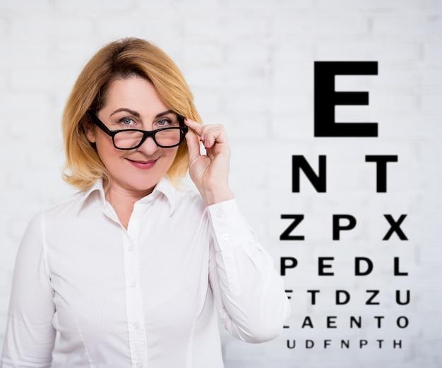 Donna d'affari matura in occhiali e diagramma di prova della vista su sfondo muro bianco