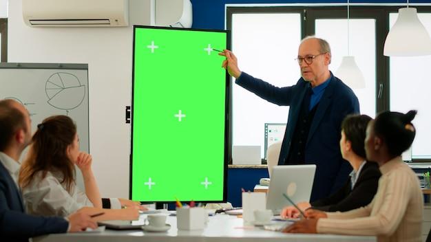 Uomo d'affari maturo che analizza i rapporti finanziari annuali in piedi nella sala conferenze che punta al monitor dello schermo verde. leader che spiega la strategia del progetto utilizzando il display chroma key del mockup del pc nella sala riunioni