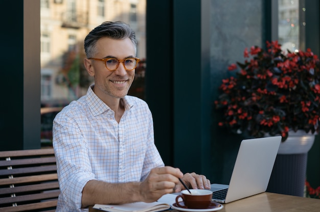 Uomo d'affari maturo che beve caffè nella caffetteria. concetto di pausa caffè