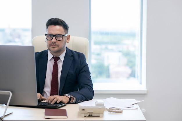 Uomo d'affari maturo in occhiali e vestito che lavora davanti al computer