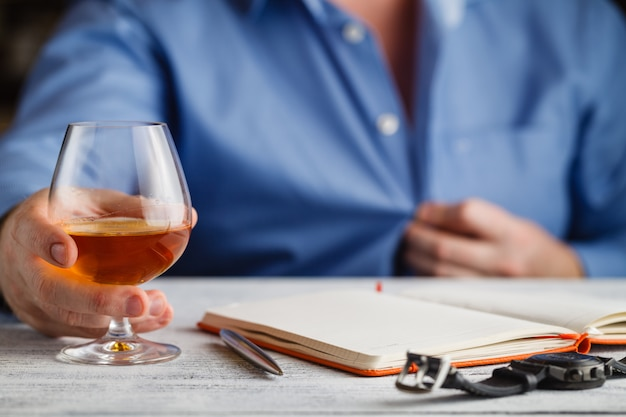 Uomo d'affari maturo che tiene un bicchiere di whiskey in hotel