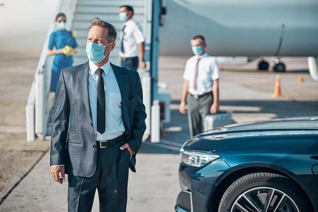 Uomo d'affari maturo è in piedi vicino all'auto mentre hostess e pilota lo stanno incontrando sulle scale dell'aereo