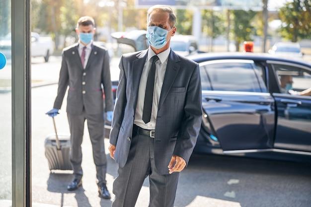 L'uomo d'affari maturo in giacca e cravatta sta andando in viaggio e l'autista lo sta aiutando con i bagagli nel terminal