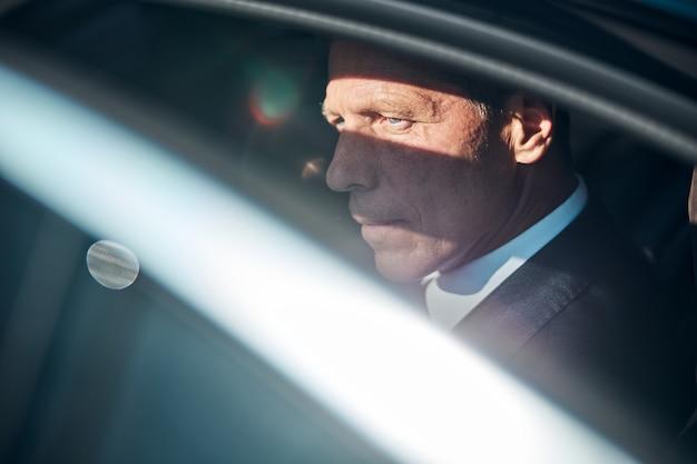 Uomo d'affari maturo in tuta sta guardando fuori l'automobile mentre viaggia con autista in una giornata di sole