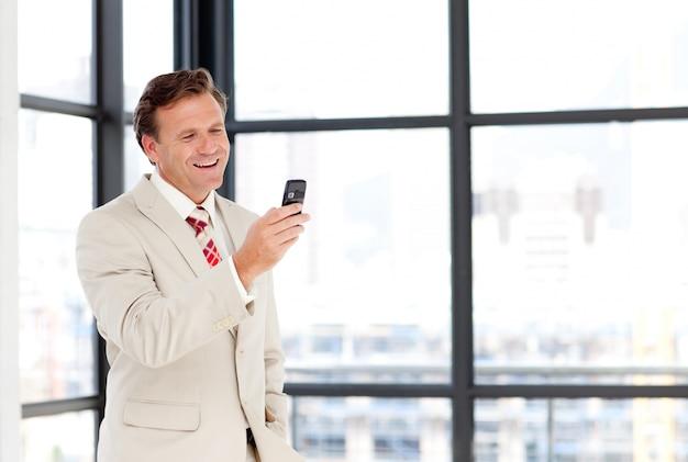 Uomo d'affari maturo che manda un sms con copia-spazio