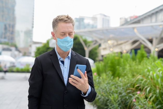 Uomo d'affari maturo che utilizza il telefono con maschera per la protezione dall'epidemia di coronavirus in città all'aperto